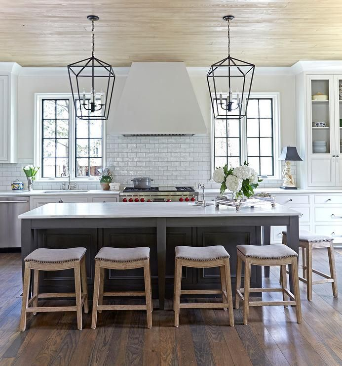 White cabinets accented with nickel hardware, white glossy subway tiles and raised panels, lends a timeless traditional style in an elegant kitchen.