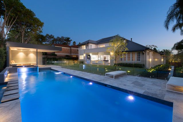Exterior and outdoor pool at night - Chateau Architects + Builders
