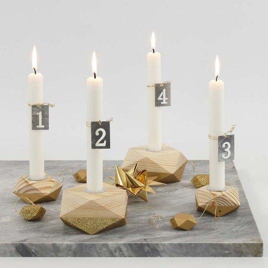 Denne adventsstage er fire lysestager i geometriske former - dekoreret partielt med guldmaling og glitter. Stearinlysene er numerisk dekoreret med små zinkskilte, fæstnet med bonzaitråd i guld.