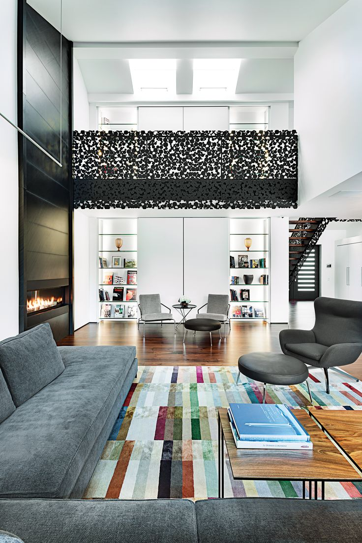 Interior designer René Desjardins elevated the spirit of a reconstructed 1960s suburban home in Montreal while tripling its square footage. Desjardins sourced all the main furniture pieces from Minotti, including a Jensen armchair and Mitchell coffee table. Spicing up the dark color palette is a striped Spectrum rug by the Rug Company. The designer chose subtle, gallery-like lighting by EKLIPSE Architectural Lighting: LED rails and back-lit niches complement the owners' art.