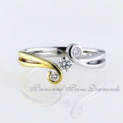 There are 3 = 0.26ct GH/VS – SI round brilliant cut diamonds tension and half tube set in a two-tone 18k white and yellow gold curly split band ring