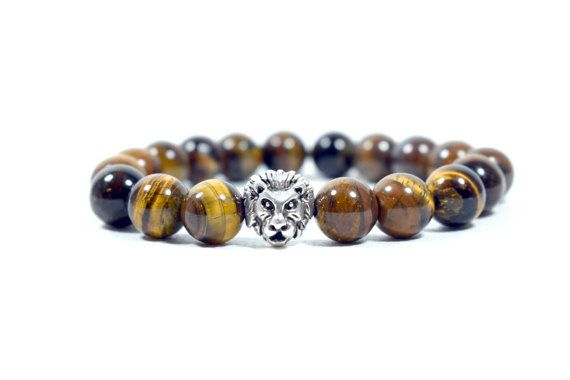Men's Protection, Fortune & Strength Bracelet, with Semiprecious Tiger's Eye beads and a Gunmetal Lion's Head bead.  This elegant Bracelet is an excellent personal accessory for the Boho Man. Made from AA Grade 10mm Tiger's Eye Beads on high quality transparent stretch cord.    A great handmade gift with style & character, for yourself or for people you love. Comes with a beautiful small gift bag!    Details:    10mm Tiger's Eye Beads  Silvertone Metal Lion Head  Quality Transparent Stretch…