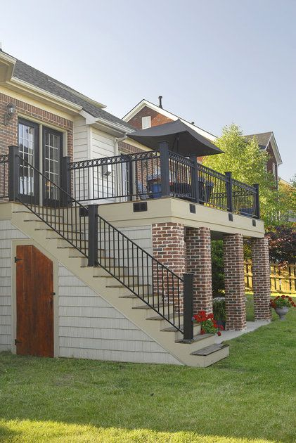Elevated deck w/ patio below, love the brick columns and the ornate step handrails! #steps #handrails