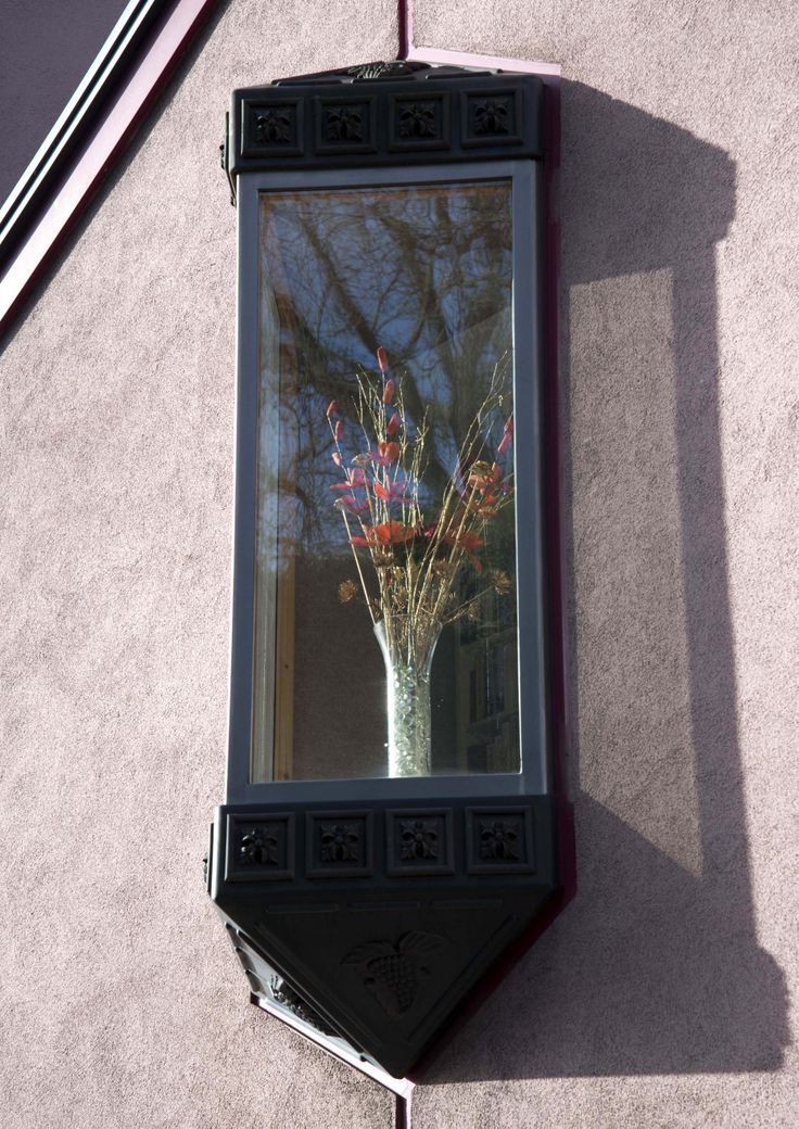 The reflection of the trees in the glass are free while the flowers in the vase are trapped inside.