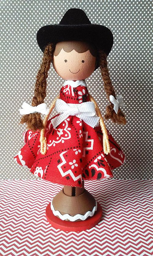 Cowgirl Ella, a super cute wooden clothespin doll stands just over four inches tall, and is uniquely hand painted in vibrant colors and wears a real cotton fabric bandana print dress.