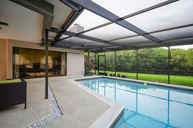 Backyard patio and pool with glass roof and wall creating a year-around swimming pool.