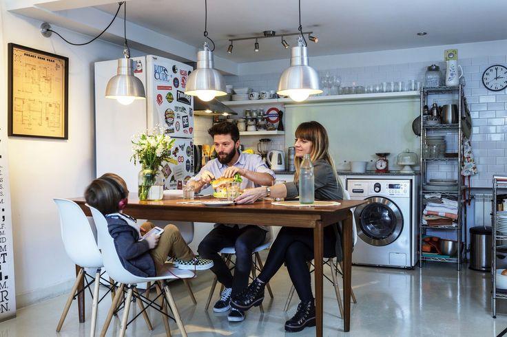 Cocina comedor de un departamento con piso de cemento alisado, revestimiento de subway tile blanco, una campana de acero inoxidable y dos estanterías de guardado.