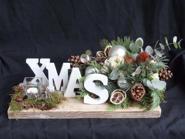 Kerststuk XMAS op een steigerhouten plank. met de letters van Actions