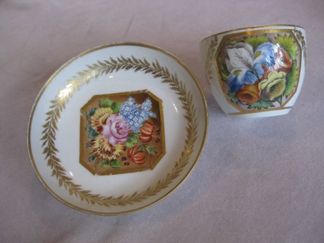 A ,possibly, Caughley cup and saucer and decorated at Mansfield with an octagonal gilt reserve containing  a group of coloured flowers and a gilt laurel border and giltrims. Billingsley decoration? Circa 1800