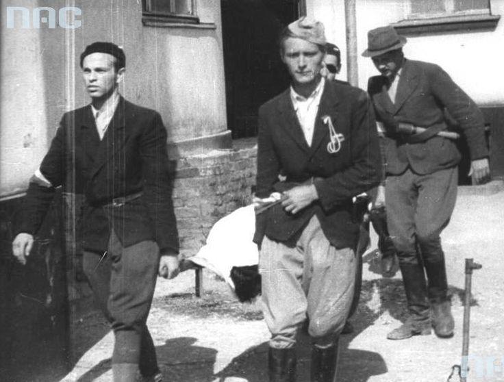 "Soldiers Squadron ""Jeleń"" in Mokotów carry the body of a fallen lieutenant. Stanislaw Jenike ""Hanski"" (5 August 1944).. From left to right: lancer Cadet. Jozef Jezierski ""Aksak"" st. Lancer Cadet. Wladyslaw Grabiński ""Pilawa"" NN, st. Lancer Cadet. Pawel Mankowski ""Rapier""."