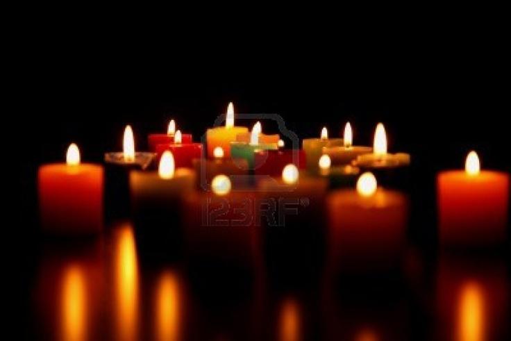 Kaarsen rond de kist. Na de uitvaart aan iedereen een gebrande kaars meegeven