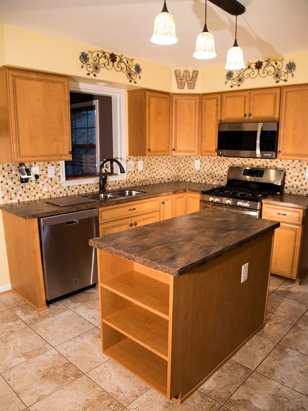 These kitchen cabinets required some structural repairs before being refaced in Italian laminate. These Cortina doors hold several helpful features such as a rollout and knife block/cutlery divider. Refaced by Kitchen Saver www.kitchensaver.com