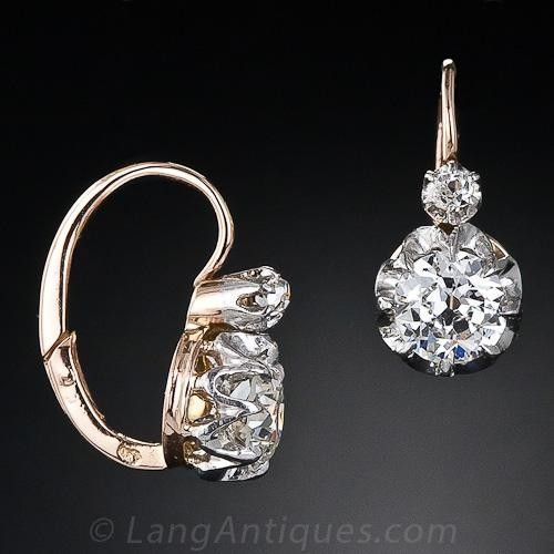 The perfect pair of antique diamond earrings from the turn-of-the-century. These earrings feature both an old European and old mine-cut diamond set in platinum over 18 karat yellow gold with a front clasping hinge. The diamonds drop just below the ear. French hallmarks, circa 1900.