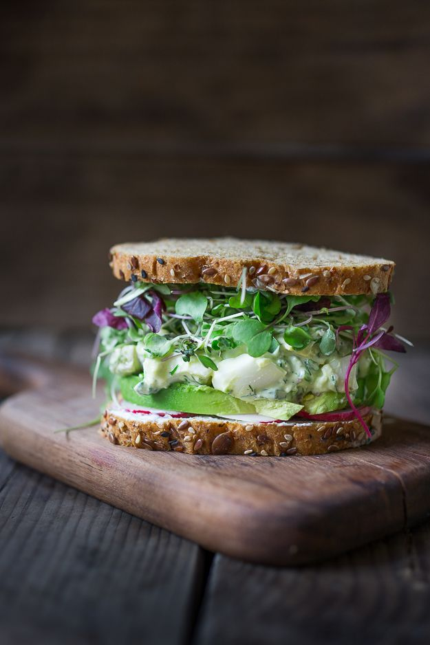 A delicious recipe for Green Goddess Egg Salad Sandwich with avocado and sprouts served on wholesome bread.