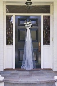 spruced up front door for a bridal shower. Used about 5 yards of tulle, silk flowers and ribbon. Looped tulle through door knocker.