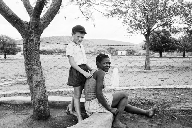 A farmer's son with his nursemaid, Heimweeberg, Nietverdiend, 1964. Photo by David Goldblatt. Goldblatt is a South African photographer noted for his portrayal of South Africa during the period of apartheid