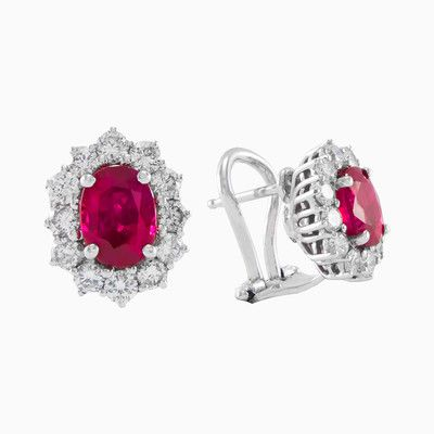 A fine pair of ruby and diamond cluster earrings, the oval shape of the coloured stone framed in a dazzling border of round brilliant cut diamonds. Is made entirely by hand in 18k white gold, total weight of diamonds is 1.00 ct and 2.00 ct total weight of natural ruby