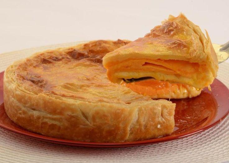 A Torta folhada de queijo está posta sobre um prato vermelho. Uma fatia está sendo tirada por uma espátula e o queijo cheddar que recheia a torta, está derretido.