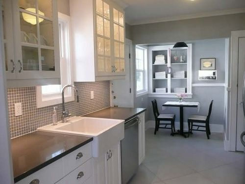 small kitchen opened up to small dining room. Gray tile, dark countertops, white cabinetrylove the color scheme