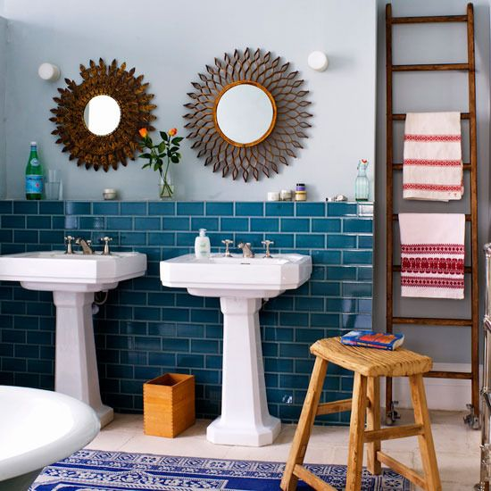 eclectic bathroom with pedestal sinks and ladder towel rack