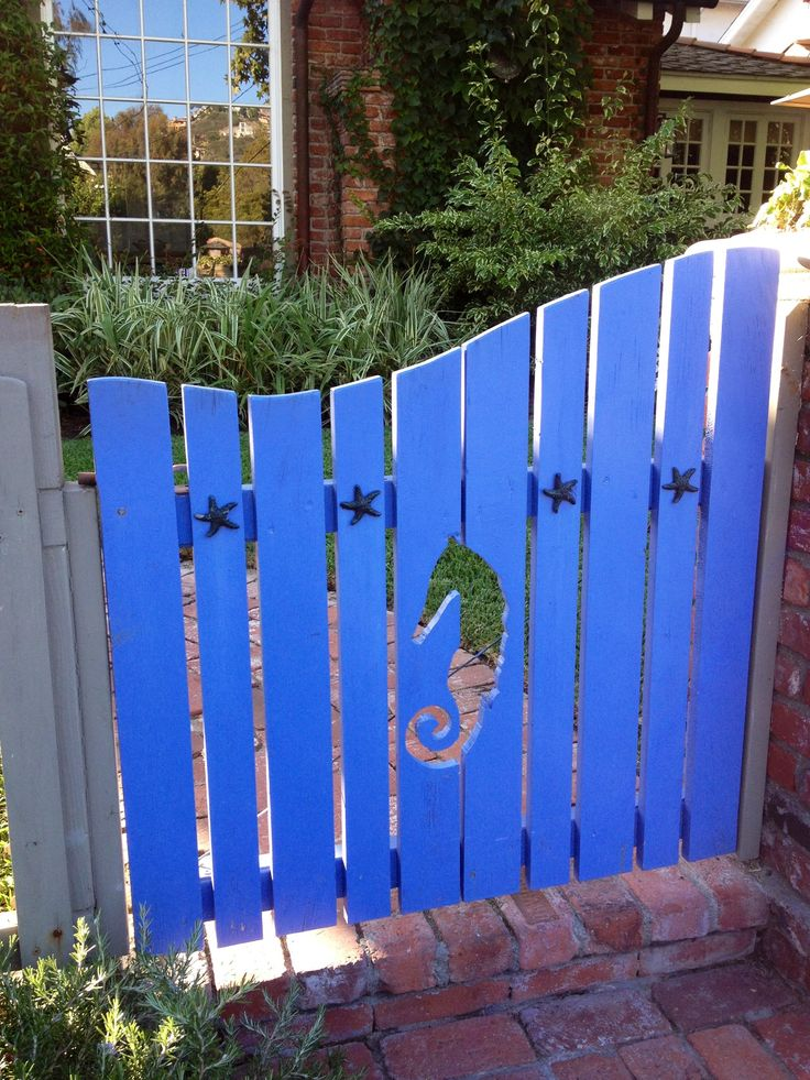 Blue garden gate with seahorse cutout & starfish.