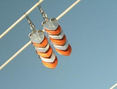 Tyto náušnice jsou vyrobeny ze šupin a kroužků z eloxovaného hliníku. Jsou lehoučké a cinkají. Barevně jsou stálé.  Zavěšené na háčku z chirurg. oceli. Barva stříbrná s oranžovou.  Celková délka i s háčkem 7,5cm. Na přání vám je mohu zkrátit.