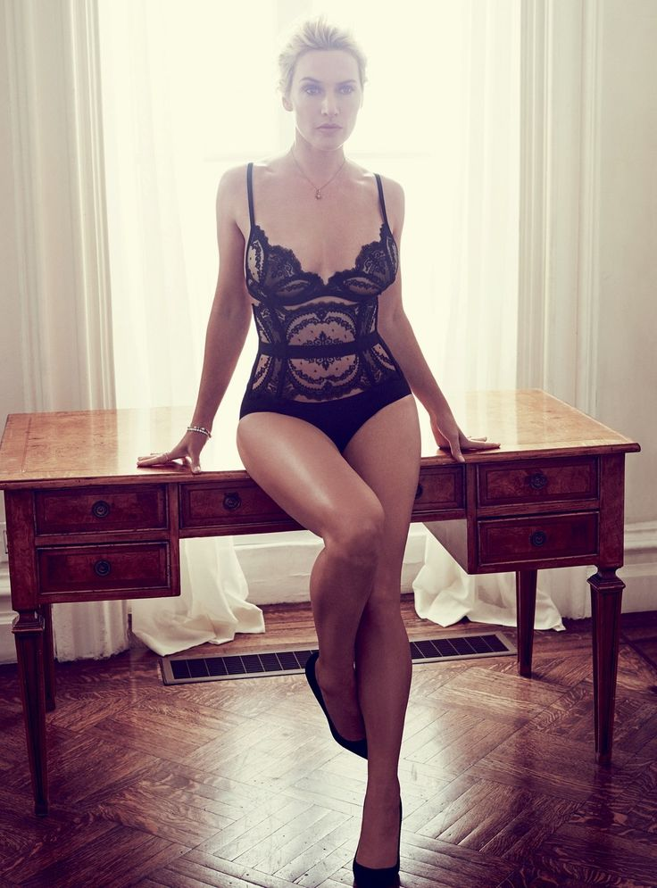 Kate Winslet leggy sitting on a desk in a onesie and high heels