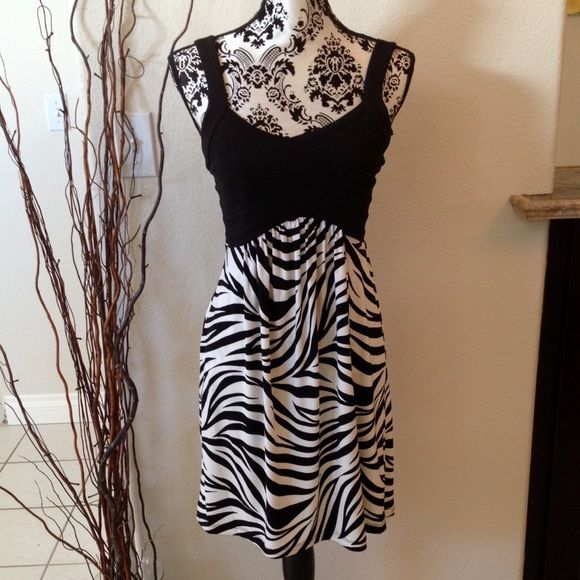 Zebra pattern short dress. Fun and sexy!! Cute A-line style short dress. Black bandage style fitted top attached to loose zebra pattern skirt. Like new. Tagged large but runs closer to medium. Sweet Storm Dresses
