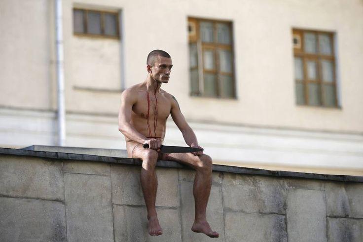 L'artista Pyotr Pavlensky sul muro dell'ospedale psichiatrico a Mosca, mentre si taglia parte di un orecchio durante una performance (Reuters)