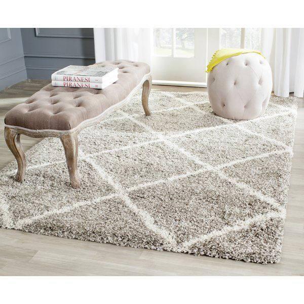A wavy diagonal plaid motif in ivory brings new cachet to a timeless gray shag texture in the fashion-forward area rug.Power-loomed of easy care polypropylene yarn, this plush shag rug is crafted with a dense, deep pile for luxury underfoot.