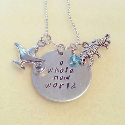 This necklace is handcrafted using a 2.5mm aluminium disc, stamped with the quote A Whole New World. It is completed with Tibetan silver