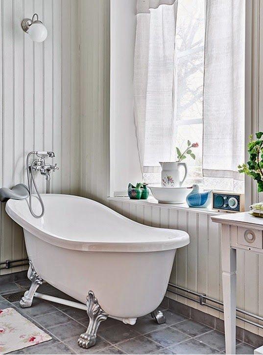 Badrum med träpanel, fönster och badkar