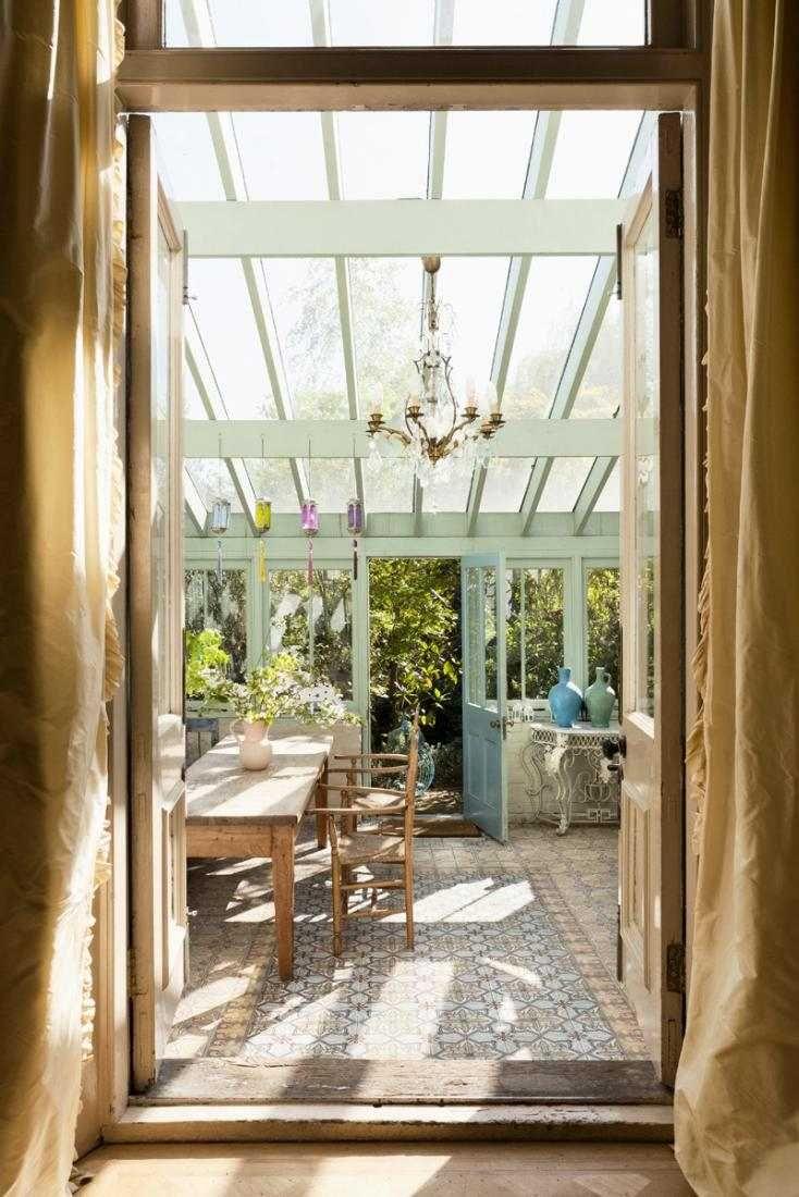 jardin d'hiver claire avec tapis et mobilier en bois rustique