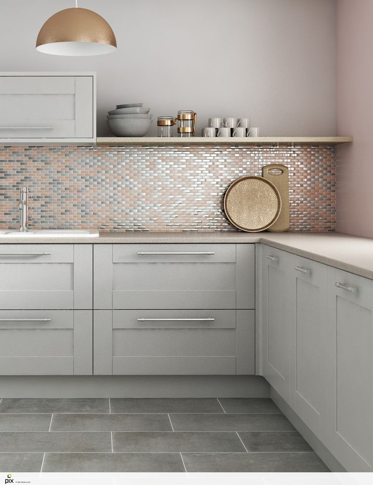 This on trend blush copper and metallic mosaic tile shot has a refined sophisticated look. The simple light grey shaker kitchen doors are teamed with slate grey floor tiles and a solid quarts worktop. Key shapes are picked out with mixed metallic finishes from the brass storage jars to the copper pendant light and chrome bar handles. An inspirational kitchen that is on trend for 2017