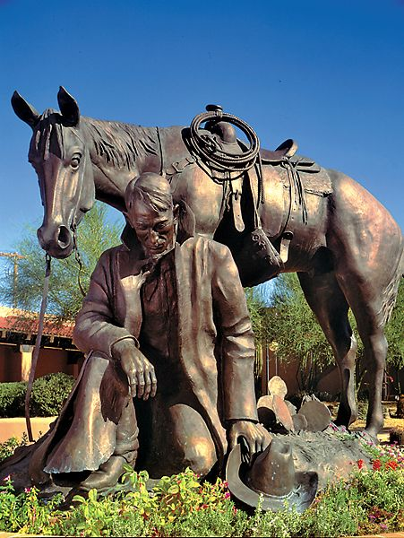 Thanks for the Rain | Artist: Joe Beeler | Year: 1988 | Where:  Wickenburg, Arizona | Why You Need to See it: This grateful cowboy kneeling in front of his horse touches pretty much everyone who sees the bronze.