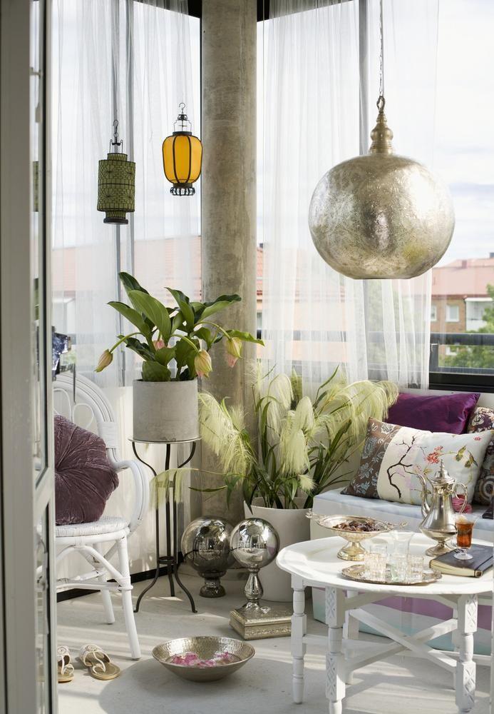 Pendelleuchte aus Metall und weiße Sitzgruppe auf dem Balkon