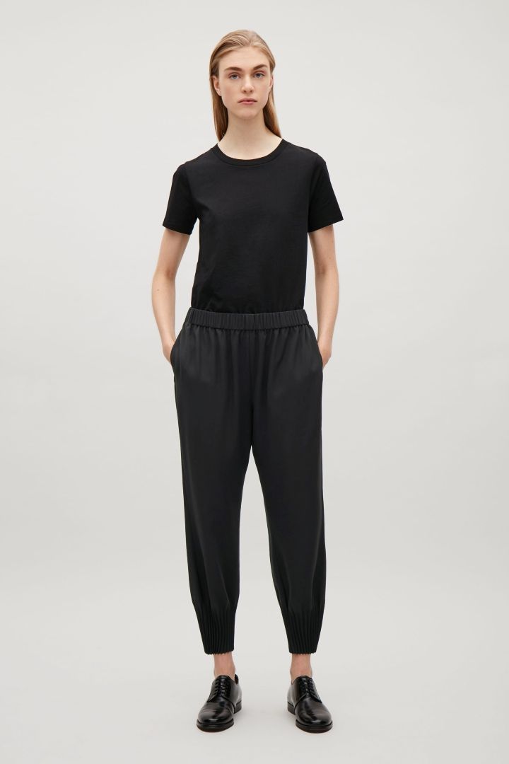 COS image 1 of Trousers with pleated hems in Black