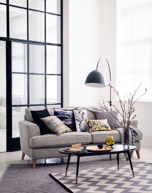 A modern living room showcasing a grey sofa with printed monochrome cushions, a contemporary coffee table, a floor lamp and a monochrome rug.