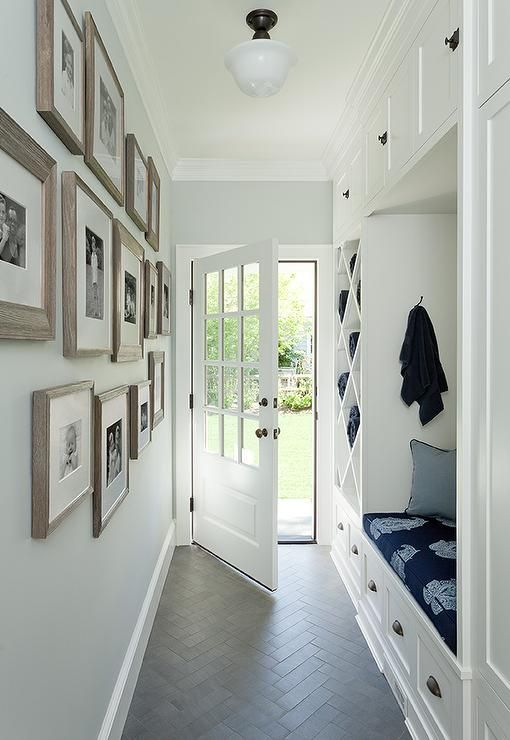 White and blue long mudroom clad in gray herringbone floor tiles is equipped with drawers donning bronze cup pulls positioned beneath a built-in bench topped with a navy blue paisley seat cushion accented with blue pillows.