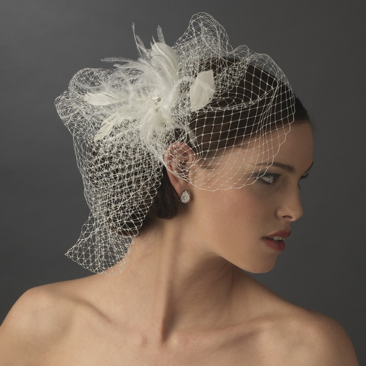 """Couture Facinator Veil Simply breath taking, this couture feather fascinator and birdcage veil has a beautiful Rhinestone Jeweled Center Accent, with a spray of feathers. This piece is worn in the hair with a comb, for a secure and comfortable fit. Available in White or Ivory. Please choose color option above.    Size: Feather Accent Measures About 5"""" Wide x 4"""" Tall"""