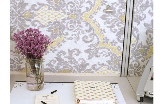 """Cover cubicle panels with """"wallpaper."""" To attach the fabric to the panels, begin pinning (with sewing pins) from the middle, moving outward. Fold the edges over and pin in place. If you're picky about edges, use a cotton ribbon to finish them off."""