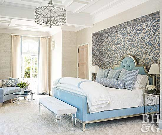 There's something regal about this elegant bedroom: the massive bed situated just so between the cut-out wall, its towering headboard upholstered in a smooth velvet, a high ceiling, and a chandelier dripping with style. A big comfy mattress doesn't need to be dressed in anything more than clean, white sheets and comforter. The room's symmetry gives every decorating decision double impact, from the pairs of pillows and a bench at the foot of the bed to the window shades and nightstands. The…