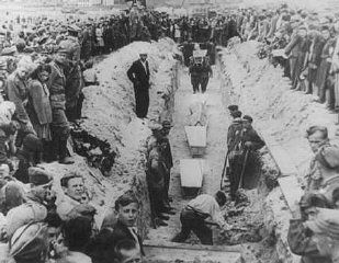 Mourners crowd around a narrow trench as coffins of pogrom victims are placed in a common grave, following mass burial service. Kielce, Poland, after July 4, 1946.