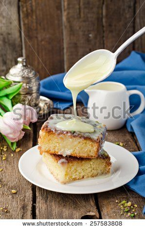 Basbousa (namoora or revane) - semolina cake with condensed milk on wooden background - stock photo