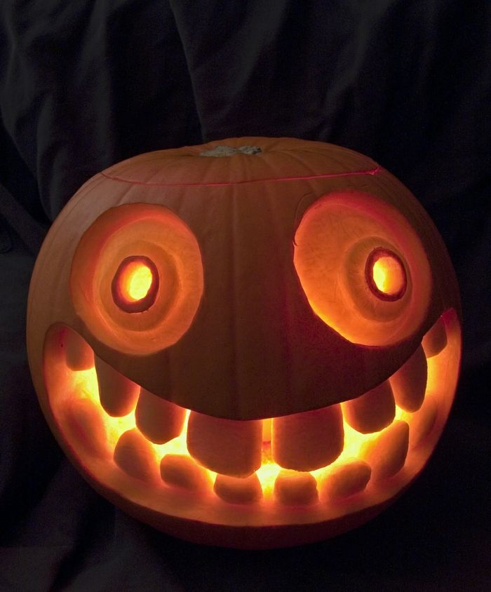como vaciar una calabaza, calabaza tallda con cara sonriente, dientes grandes, iluminada por dentro