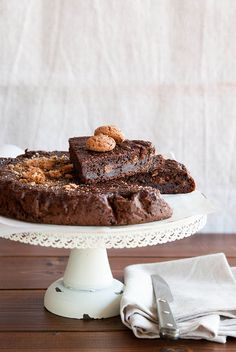 Torta di pane al cacao: - 200 gr. di pane raffermo - 500 gr. di latte - 120 gr. di zucchero - 120 gr. di amaretti - 120 gr. di uvetta - 2 uova - 2 cucchiai di rum scuro - 30 gr. di cacao amaro - 30 gr. di mandorle - Buccia grattugiata di mezzo limone biologico - 1/2 bustina di lievito per dolci - Sale un pizzico