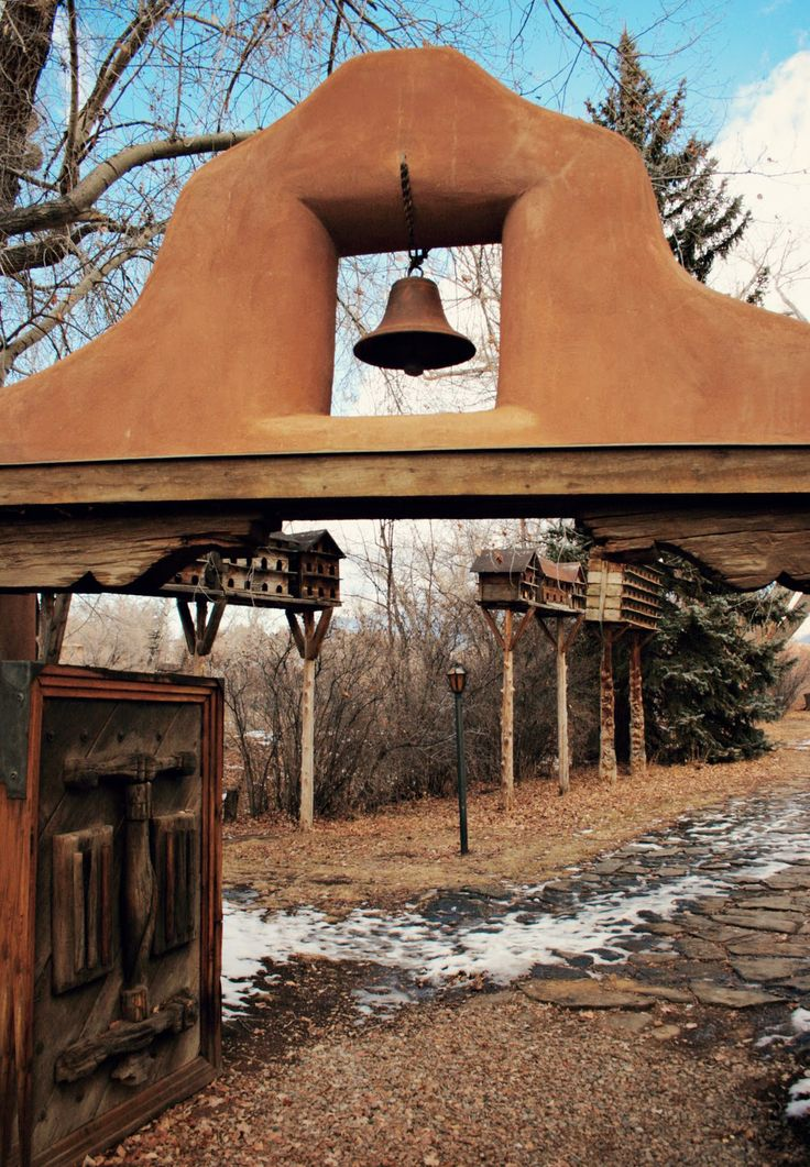 Mabel Dodge Luhan house in Taos...love everything about this photo...pine tree, birdhouses, adobe entryway, gate, bell, corbels, gate, snow, flagstone...