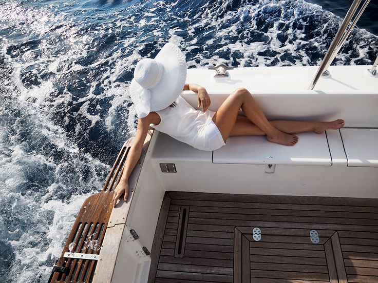 anouska lying on a boat in monaco wearing all white sunhat