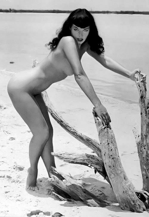Una conturbante Bettie Page posa nuda in spiaggia. <3