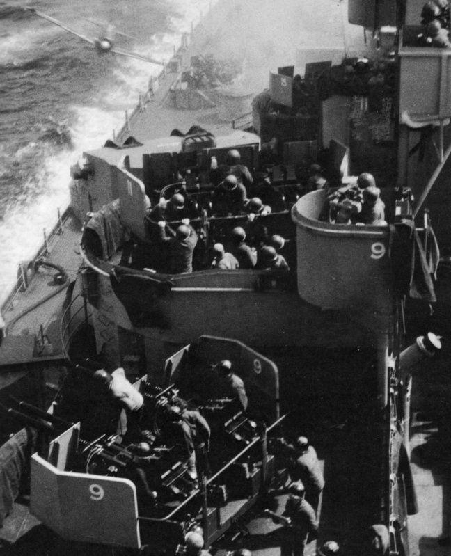Японский камикадзе на истребителе A6M «Зеро» врезается в американский линкор «Миссури» (USS Missouri (BB-63) во время участия последнего в битве за Окинаву. Самолет ударил в корабль ниже главной палубы, причинив небольшие повреждения и не вызвав жертв. На переднем плане — расчеты 40-мм счетверенных зенитных установок.